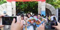 资料图:2018年高考结束,家长为刚刚走出考场的孩子拍照留念。 王以照 摄 - 新浪湖北
