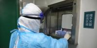 图为核酸检测员将灭活后的咽拭子样本转至输血科实验室传递窗进行交接。 代雨朦 摄 - 新浪湖北